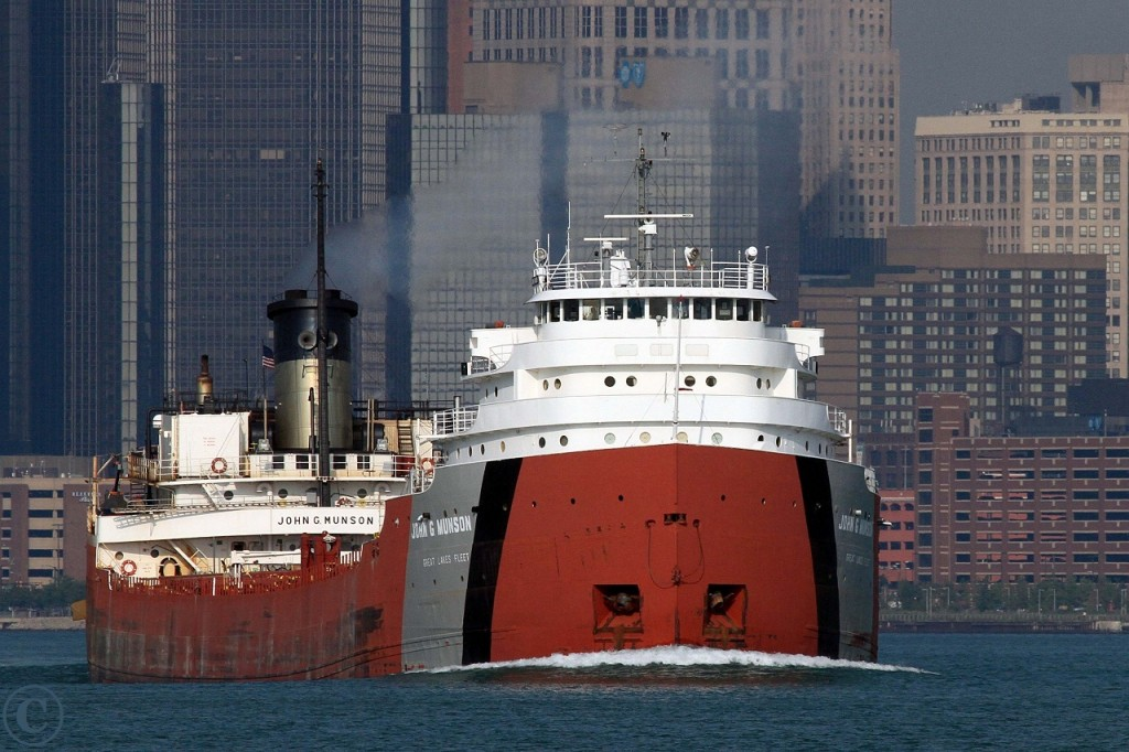 With the city of Detroit Michigan serving as a backdrop, the John G. Munson charges upbound on the Detroit River at Windsor.
