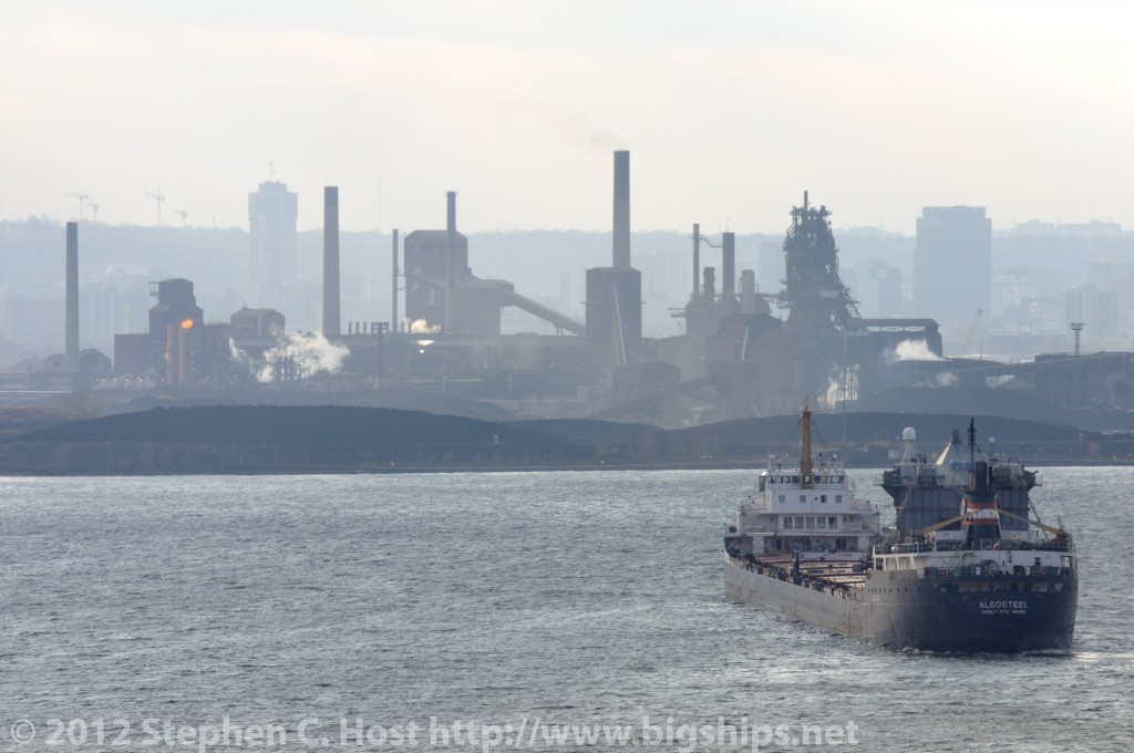 Algosteel has just entered the Burlington Bay - with a cargo of Iron Ore from the Labrador iron ore fields. The ship is turning to dock at the Steel Mills of Hamilton shown in the background.
