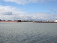 The 1004\' James R Barker, heading upriver, passes the smaller St. Clair on its namesake river at Sarnia, ON.